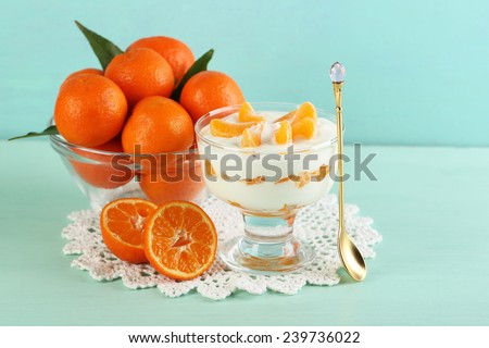Tasty milk dessert with fresh tangerine pieces in glass jar and Christmas balls, on color wooden background - stock photo