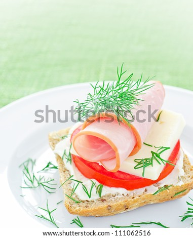 Tasty mini ham sandwich appetizer on plate - stock photo