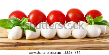 Tasty mozzarella cheese balls with basil and red tomatoes, on cutting board, isolated on white - stock photo