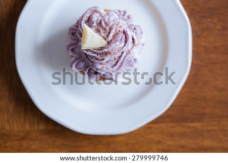 Tasty muffin with blueberry cream sprinkled with cocoa powder - stock photo