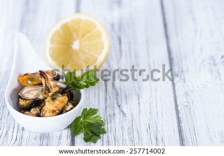 Tasty Mussels pickled on oil with fresh herbs (close-up shot) - stock photo