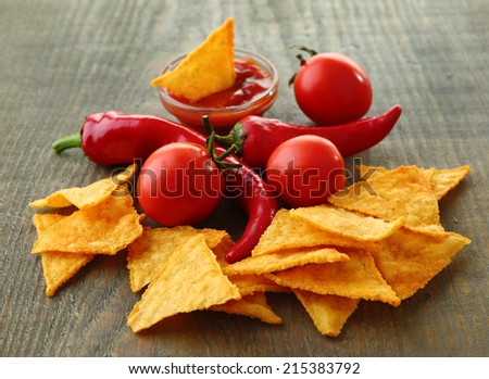 Tasty nachos, red tomatoes and chili pepper on wooden background - stock photo