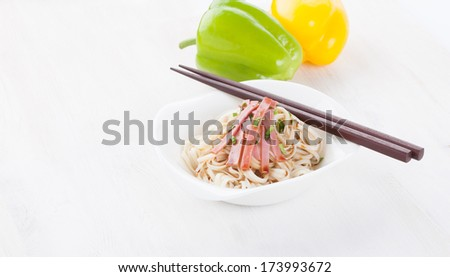 Tasty noodles with ham green onions in a beautiful white bowl on a white wooden background. Peppers and tomatoes. - stock photo