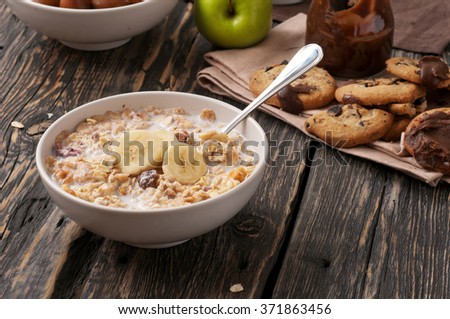 Tasty oatmeal porridge with bananas in white bowl on a dark rustic table close up with copy space - stock photo