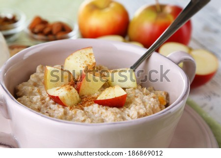 Tasty oatmeal with apples and cinnamon on table close up