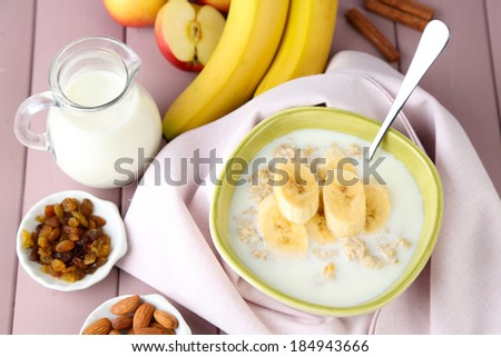 Tasty oatmeal with bananas and milk on wooden table - stock photo