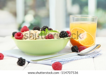 tasty oatmeal with berries and glass of juice on table, on window background - stock photo