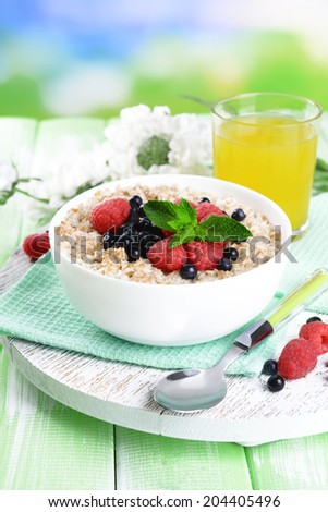 Tasty oatmeal with berries on table on bright background - stock photo