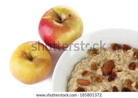 Tasty oatmeal with raisins and apples isolated on white