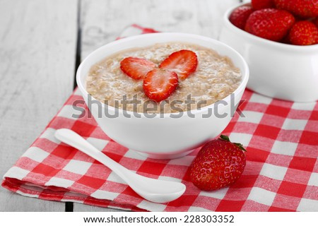 Tasty oatmeal with strawberry on table close-up - stock photo