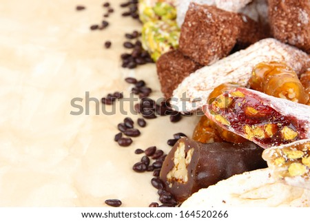 Tasty oriental sweets, on brown background - stock photo