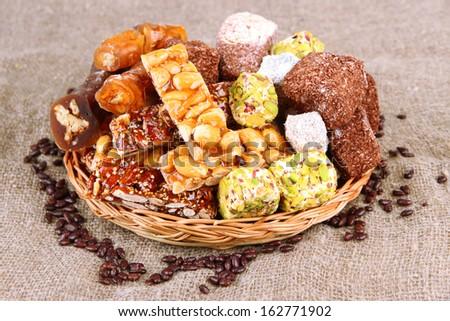 Tasty oriental sweets, on burlap background - stock photo