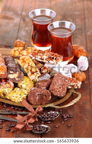 Tasty oriental sweets on tray and glasses of tea, on grey wooden background - stock photo