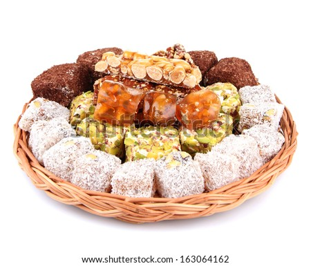 Tasty oriental sweets on wicker tray, isolated on white - stock photo