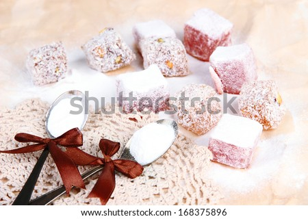 Tasty oriental sweets (Turkish delight) with powdered sugar, on brown background - stock photo