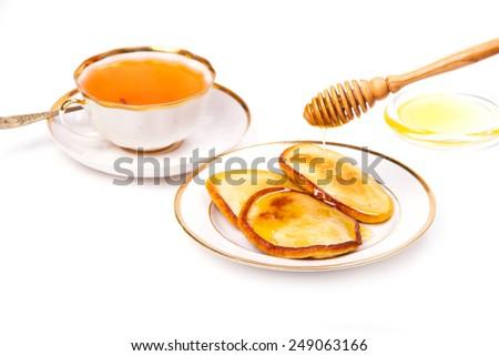 Tasty pancakes with honey and tea - stock photo