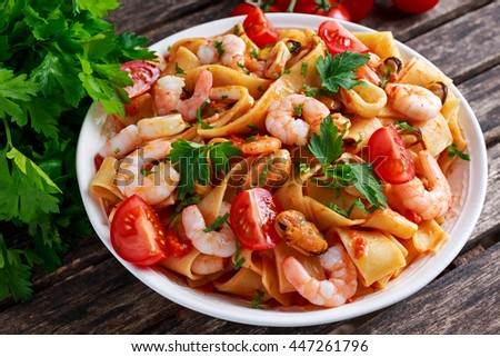 Tasty Pappardelle pasta with shrimp, Squid, mussel, tomatoes and herbs. - stock photo