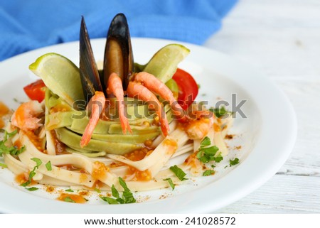 Tasty pasta with shrimps, mussels and tomatoes on plate on wooden background - stock photo