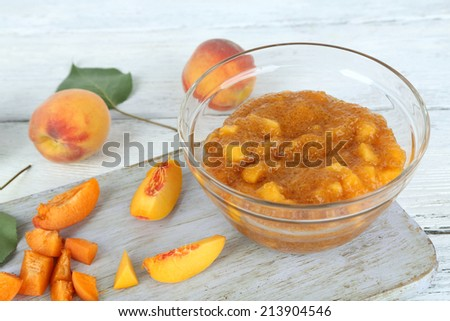 tasty peach jam with fresh peaches on wooden table - stock photo