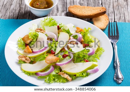tasty pear salad with walnut, red onion, lettuce leaves, and sun-dried cranberry on the white dish, selective focus, macro