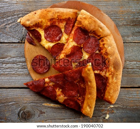 Tasty Pepperoni Pizza with Slice of Salami on Wooden Plate closeup on Rustic Wooden background. Top View - stock photo