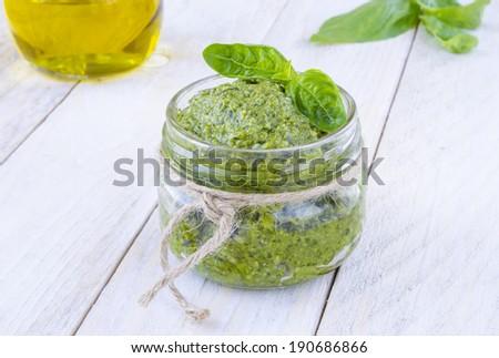 Tasty pesto sauce on white wood boards  - stock photo