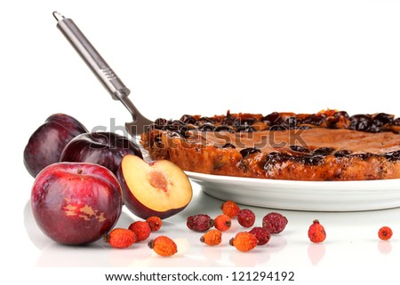 Tasty pie on plate with plums isolated on white