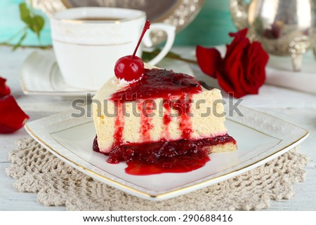 Tasty piece of cheesecake with berry sauce on plate on table close up - stock photo