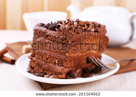 Tasty piece of chocolate cake with mint and cinnamon on wooden table and blurred planks background, closeup view