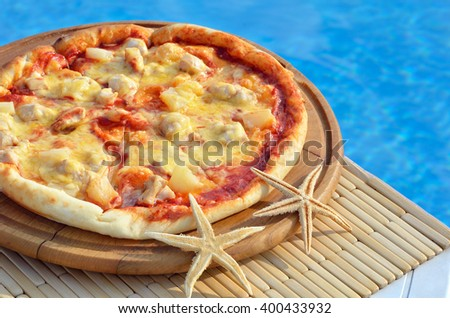 Tasty pizza decorated with starfishes on the swimming pool background