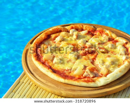 Tasty pizza on the swimming pool background