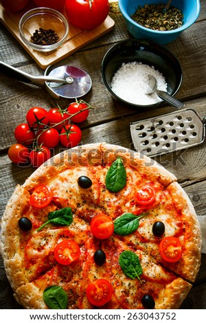 Tasty pizza, tomatoes and other products on a wooden board.  - stock photo