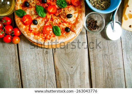 Tasty pizza, tomatoes and others ingredients on a wooden background.  - stock photo