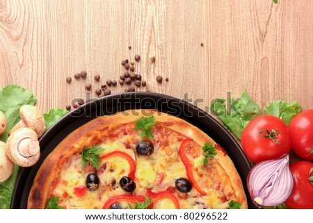 tasty pizza with olives and vegetables on a wooden background - stock photo