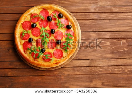 Tasty pizza with salami and olives on wooden background