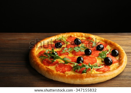 Tasty pizza with salami and olives on wooden table against black background