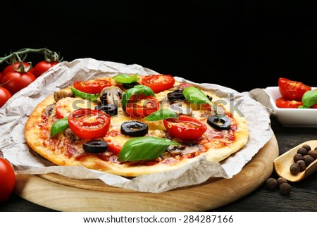 Tasty pizza with vegetables and basil on black background - stock photo