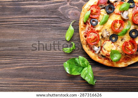 Tasty pizza with vegetables and basil on wooden background - stock photo