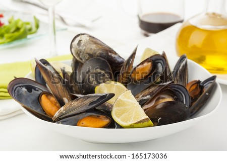 tasty plate of coocked mussels with lemon isolated over white
