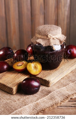 Tasty plum jam in jar and plums on wooden table close-up - stock photo