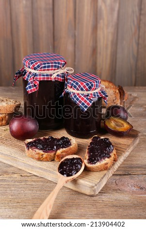Tasty plum jam in jars and plums on wooden table - stock photo