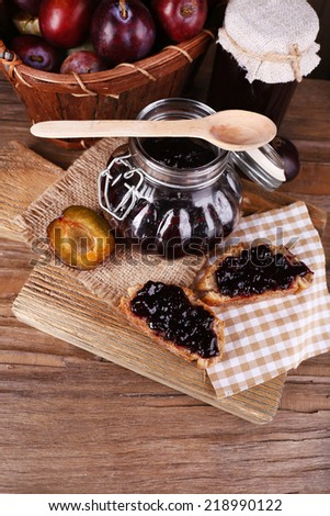 Tasty plum jam in jars and plums on wooden table close-up - stock photo