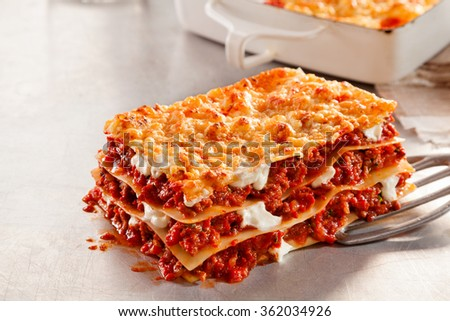 Tasty portion of freshly baked Italian beef and mozzarella lasagne on a metal spatula over a scratched white kitchen surface, close up side view - stock photo