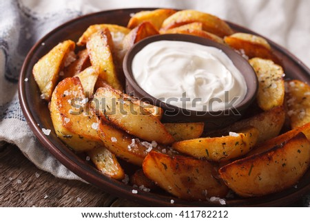 Tasty potato wedges with herbs and mayonnaise on a plate closeup on the table. horizontal - stock photo