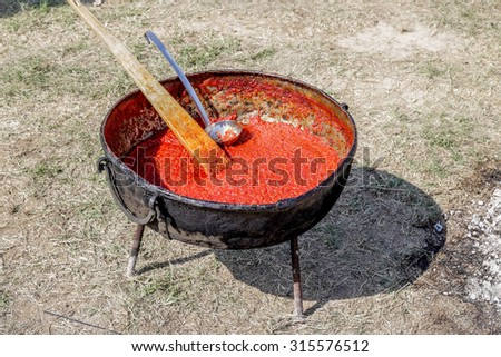 Tasty red chutney being cooked in metallic pot