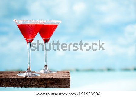 Tasty red drink on beach with ocean on sky background - stock photo