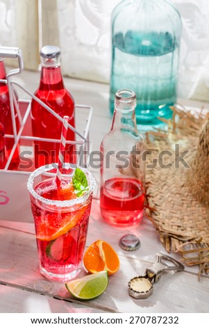 Tasty red summer drink with citrus fruit