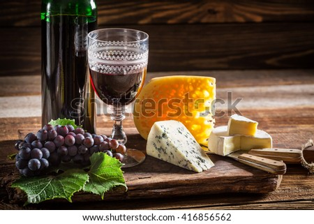 Tasty red wine in bottle with grapes and cheese - stock photo