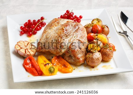 Tasty roasted loin pork with potatoes, bell peppers and gooseberries - stock photo