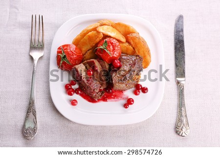 Tasty roasted meat with cranberry sauce and roasted vegetables on plate, on light background - stock photo